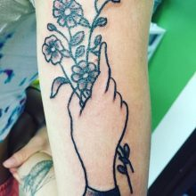 hand holding flowers tattoo by Teemu Kilz